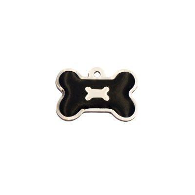 Placa para perros con forma de hueso y un hueso sobre fondo negro.